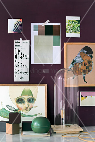 Handmade lamp under glass cover in front of pictures on purple wall