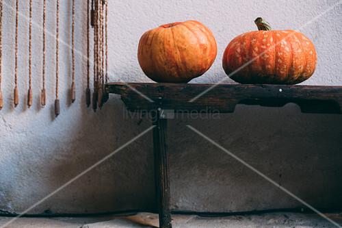 Zwei Kürbisse auf Holzbank an Hauswand