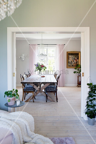 View through open sliding door into dining room with long table and various chairs