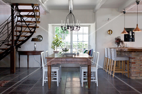 White chairs at wooden table in open-plan interior with staircase