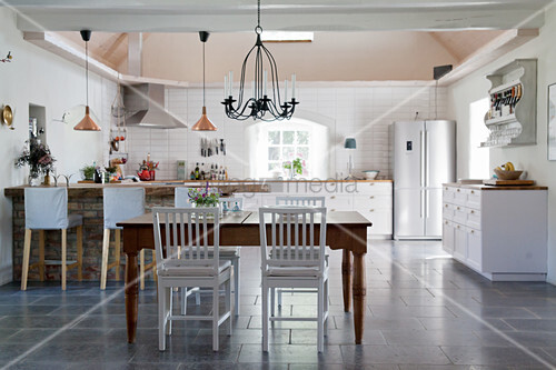 Dining table in front of open-plan, country-house-style kitchen with black floor