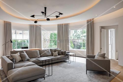 Hellgraue Polstergarnitur in elegantem Wohnzimmer mit gebogener Wand