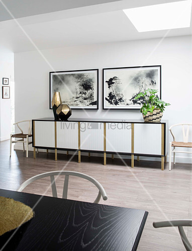 Houseplants and vases on sideboard below black-and-white pictures on wall