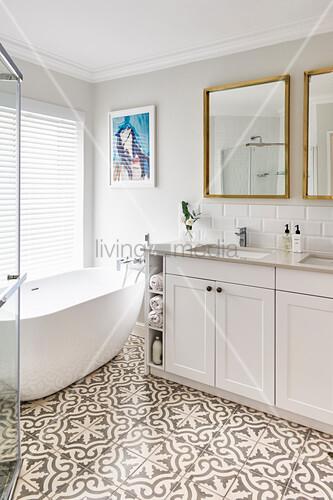 Twin washstand next to freestanding bathtub