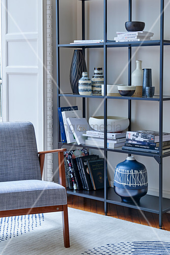Chair with grey cover next to books and various ceramic containers on open metal shelves