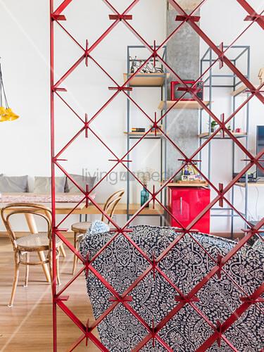 Blick durch Raumteiler auf Sessel, Esstisch und Regal
