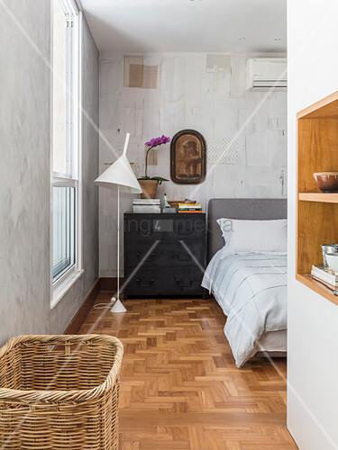 Stehlampe und Kommode neben Bett im Schlafzimmer mit strukturierter Wand