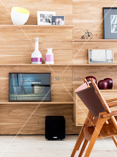 Ornaments on shelves on wood-panelled living-room wall