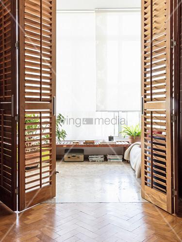 Blick durch geöffnete Lamellentüren ins Wohnzimmer