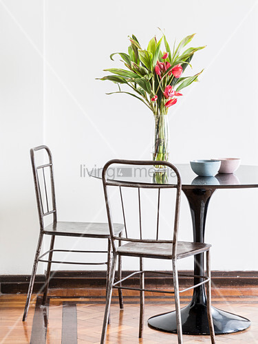 Vase of flowers on round, black table and vintage metal chairs