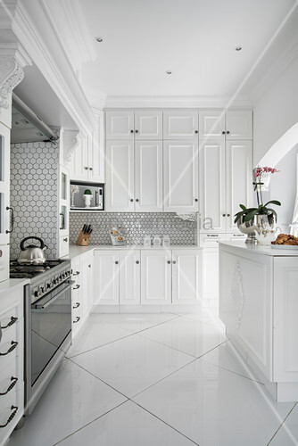 Honeycomb wall tiles in elegant, white fitted kitchen