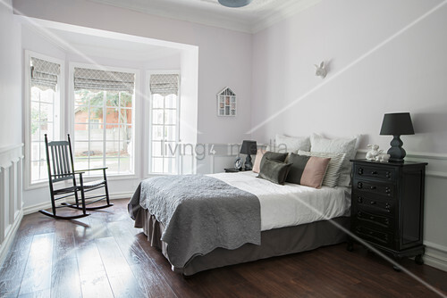 Double bed and rocking chair in guest bedroom with bay window