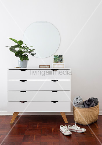 Houseplant on white chest of drawers below mirror on wall