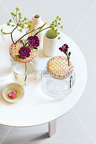 Glass jars with wicker lids as vases