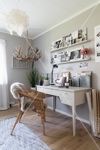White desk and wicker chair below shelves on grey wall