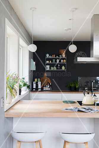 View over counter with pale wooden surface to kitchen counter against charcoal wall