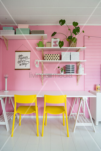 Yellow chairs at desk below shelves on pink wall