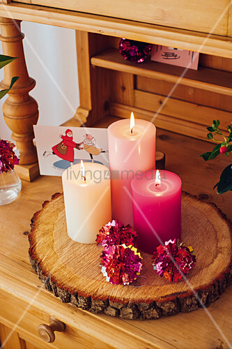 Kerzen und Kugeln aus glänzendem Stanniol auf rustikaler Baumscheibe