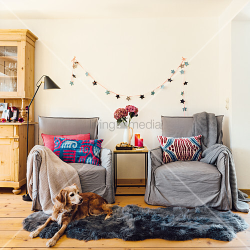 Armchairs and a side table in front of a Christmas garland with a dog lying on a grey animal fur rug