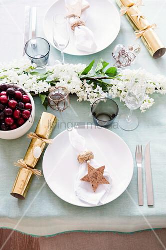Gedeckter Tisch mit Knallbonons und Blütenzweig in der Mitte