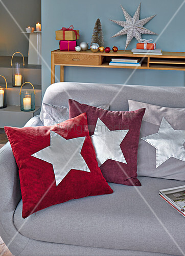 Homemade cushions with silver stars for Christmas on a sofa