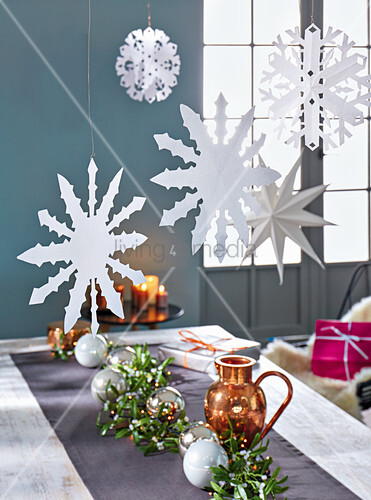 Paper snowflakes and stars hanging above a table