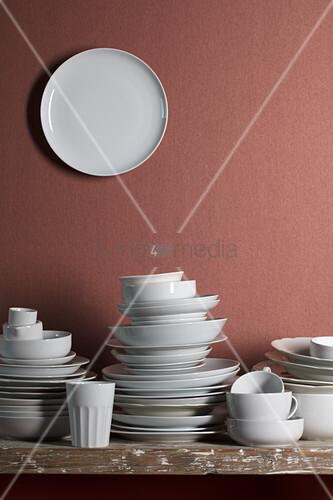 Weisses Geschirr auf Tisch und Teller an Wand dahinter