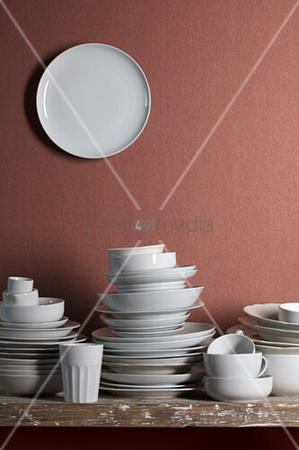 White crockery on table and white plate on wall