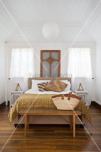Double bed, bedroom bench, symmetrically arranged bedside cabinets and white-painted wood cladding in bedroom