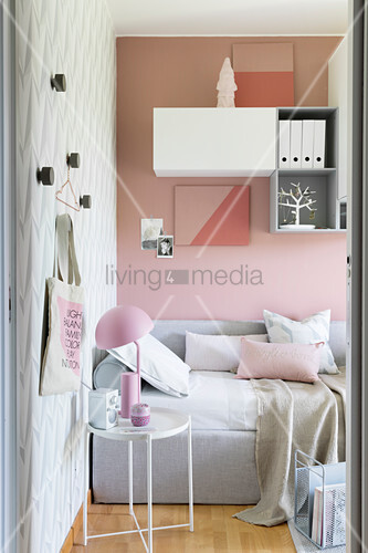 Daybed and side table in room with pink, pale grey and white accessories