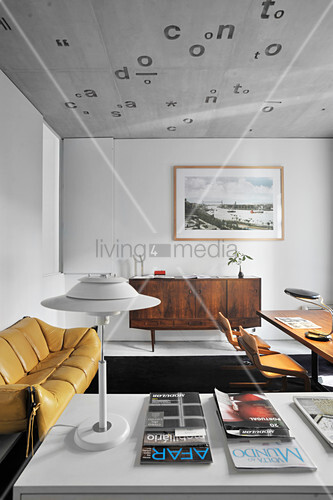 Tables, leather sofa and retro sideboard in room with concrete ceiling