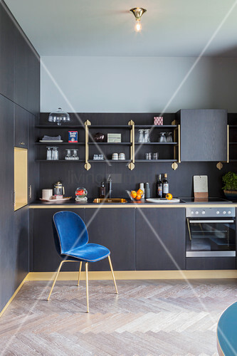 Blue velvet chairs in black kitchen with gold details
