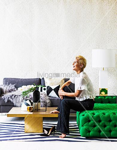 Blonde Frau sitzt auf grünem Ottoman, goldfarbener Couchtisch und graues Sofa im Wohnzimmer