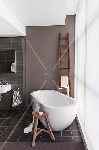 Badezimmer in Brauntönen, frei stehende Badewanne vor Polycarbonatwand