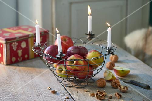 Äpfel im Drahtkorb mit vier brennenden weißen Kerzen