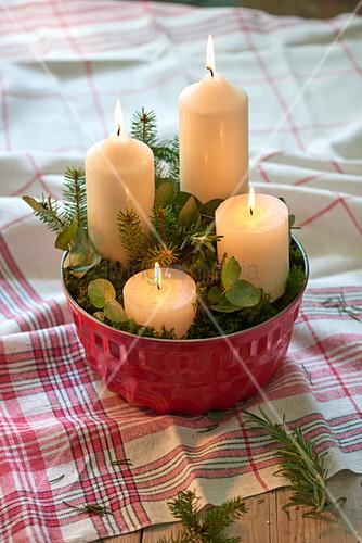 Vier weiße Kerzen in einer Gugelhupfform mit Zweigen