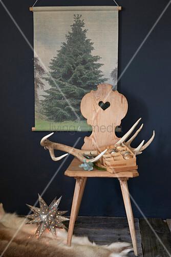 Geweih und Christbaumkugeln auf Bauernstuhl vor einem Bild
