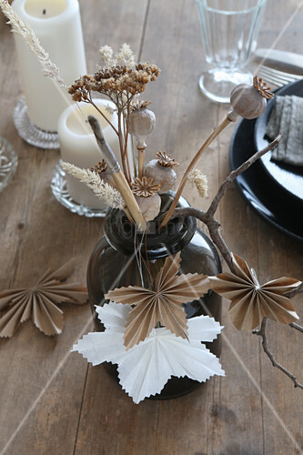 Dried flowers in vase, poppy seed heads and origami maple leaves
