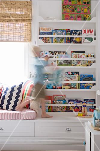 Boy walking in front of book shelves in child's bedroom
