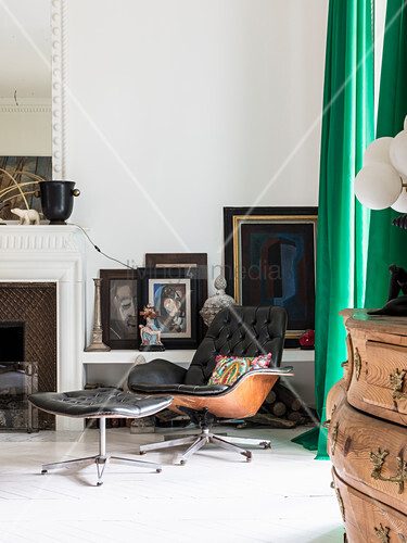 Eames Lounge Chair and footstool in front of pictures on shelf