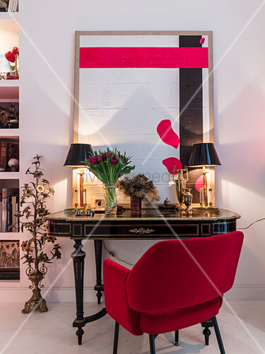 Red upholstered chair at antique table with table lamps and modern artwork