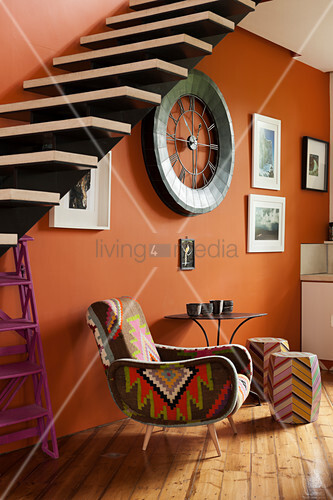 Kilim chair under a self-supporting staircase against orange wall