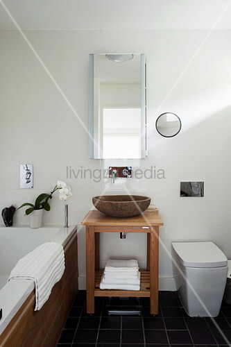 Stone washbasin on wooden washstand in bathroom with slate floor tiles