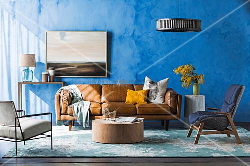 Braune Ledercouch, Sessel und Couchtisch im Wohnzimmer mit blauer Wand