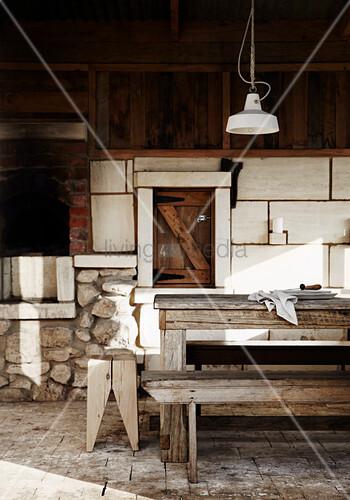 Rustikaler Holztisch und Bank, darüber Pendelleuchte