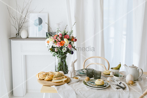Vase of colourful flowers on table set for Easter breakfast