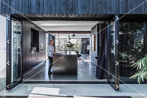 Blick durch geöffnete Falttür in offene Küche, Frau an der Kücheninsel