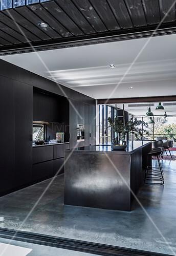 Blick in offene Küche mit Kücheninsel und Betonboden