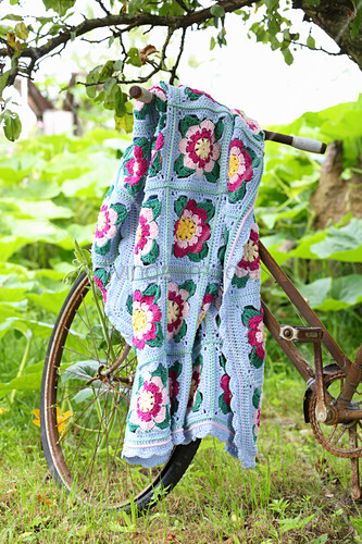 Floral crocheted blanket draped over rusty bicycle in garden