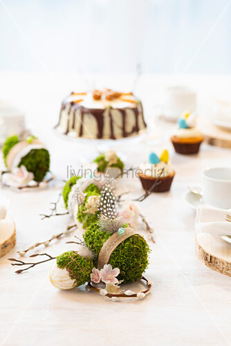Handmade concrete Easter eggs wrapped in moss decorating table